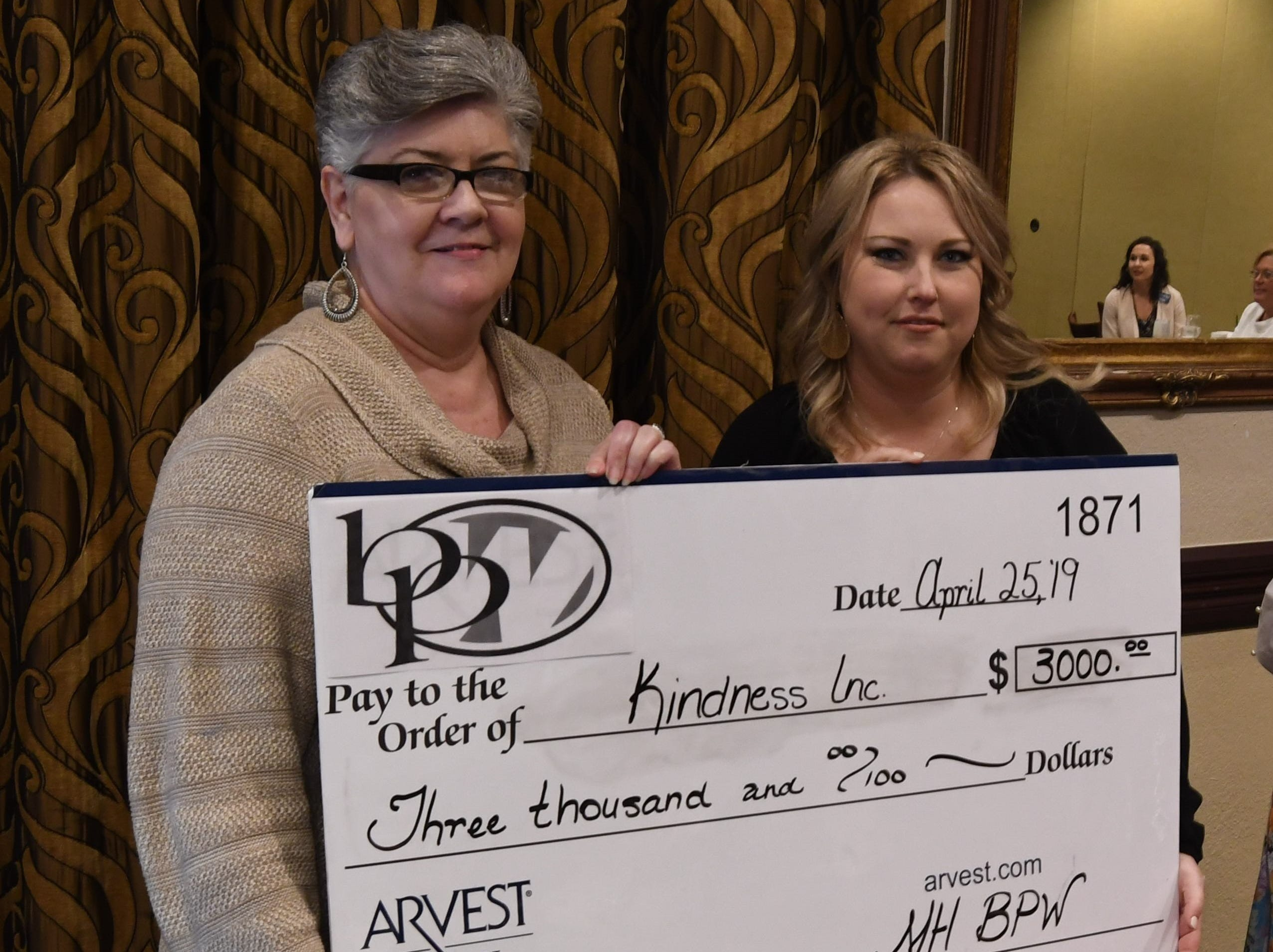 Debbie Wamock (left) accepts a check for $3,000 from Mountain Home Business & Professional Women president Ashley Hambelton on behalf of Kindness Inc.