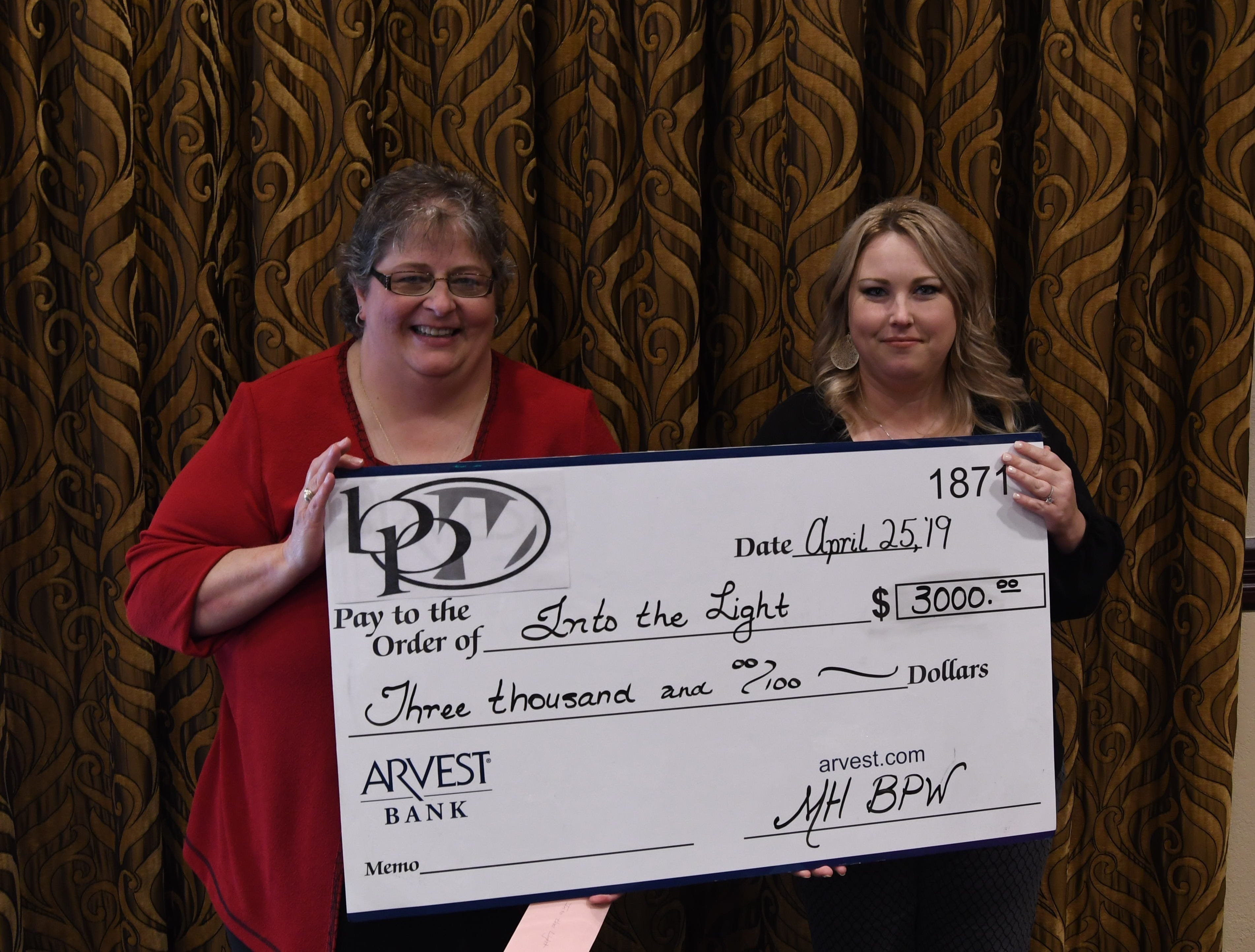 Cindy Isbell (left) accepts a check for $3,000 from Mountain Home Business & Professional Women president Ashley Hambelton on behalf of Into The Light.