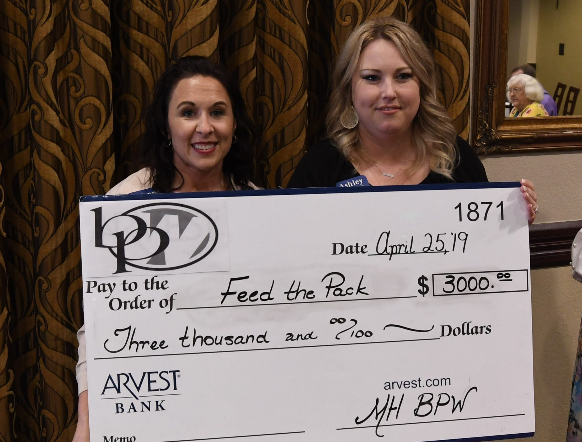 Arvest Bank's Adrienne Blackwell (left) accepts a check for $3,000 from Mountain Home Business & Professional Women president Ashley Hambelton on behalf of Feed The Pack.