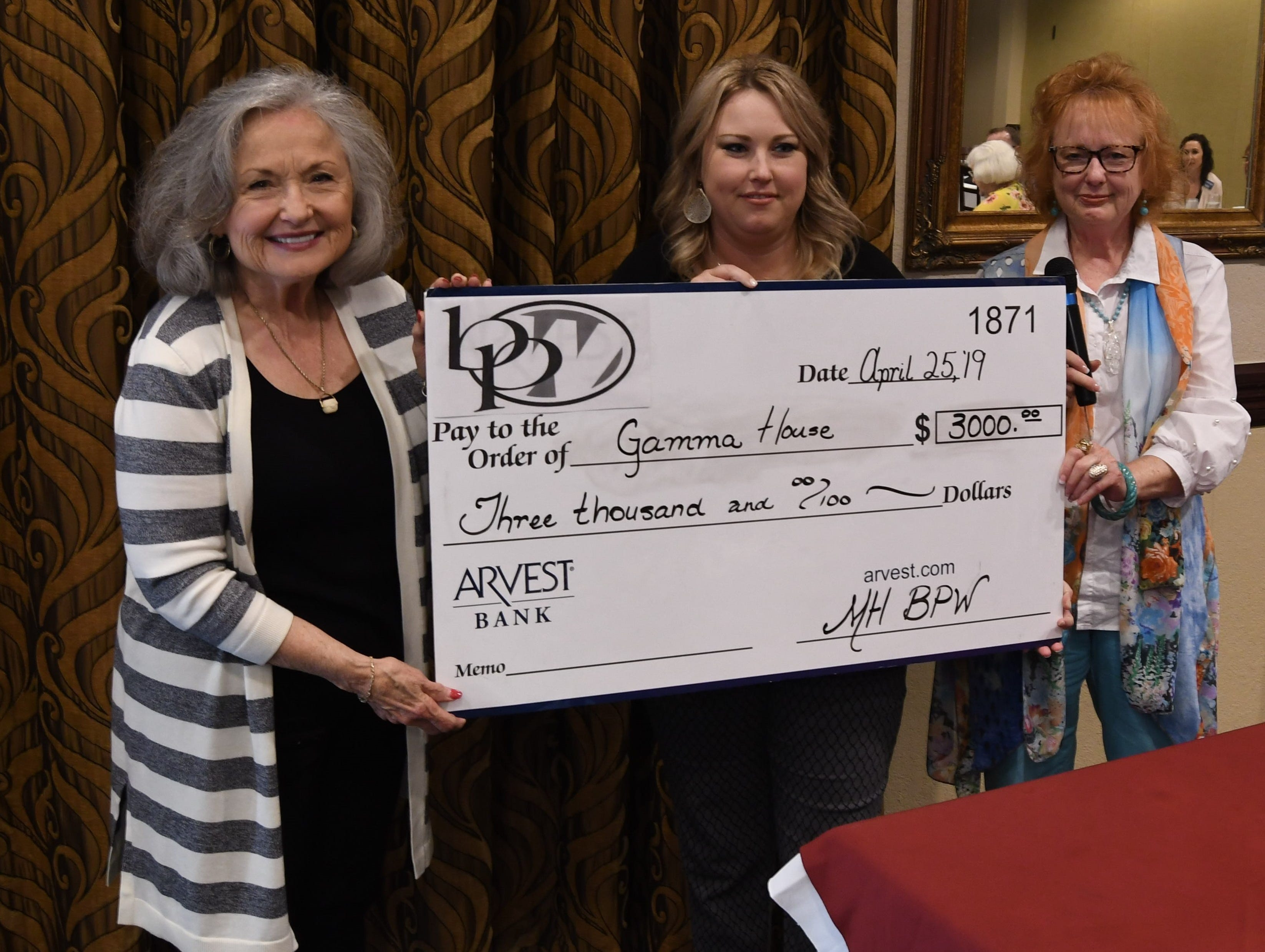 Judy Strother (left) accepts a check for $3,000 from Mountain Home Business & Professional Women president Ashley Hambelton and vice president Lucinda Blair on behalf of Gamma House.