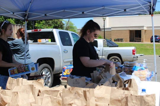 Brooke Martin prepares sack lunches with Reclaimed Outdoors LLC in Ruston Friday.
