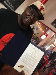 That's My Child founder Charles Lee holds a proclamation from the Alabama Senate honoring That's My Dog Jr.