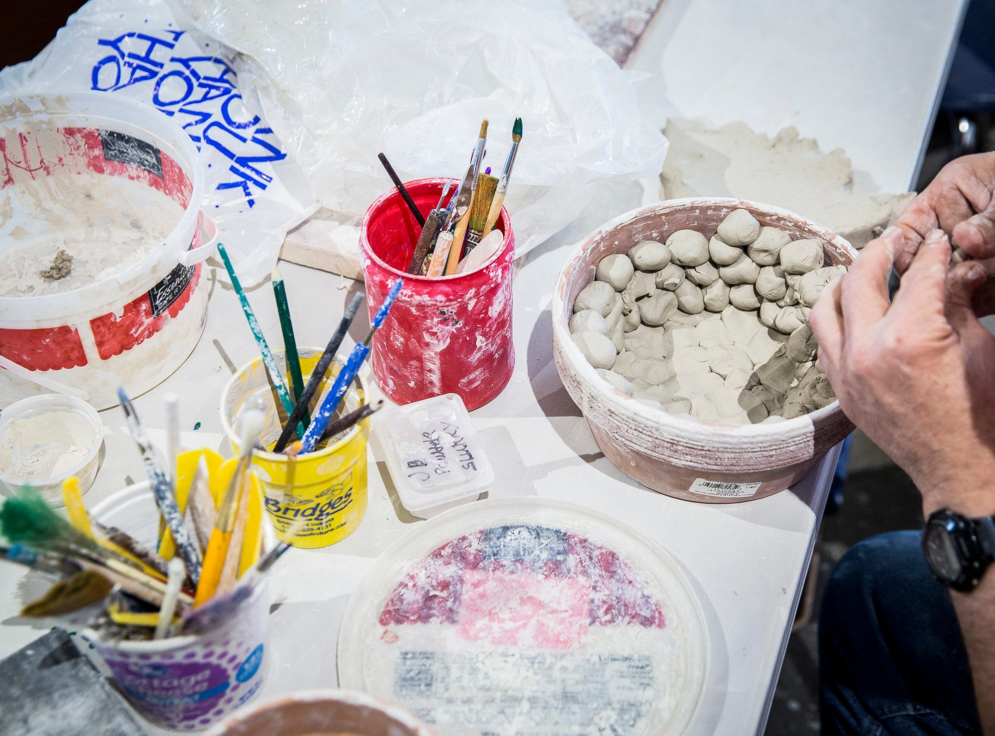 Jim Lawson creates clay planters Friday morning at Beyond I Can's new location in Madjax.