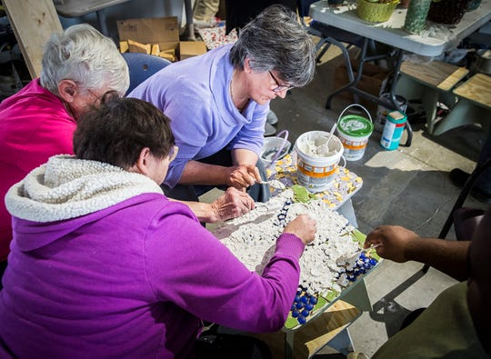 Beyond I Can workers create mosaic tile tables at the program's new Madjax location Friday morning.