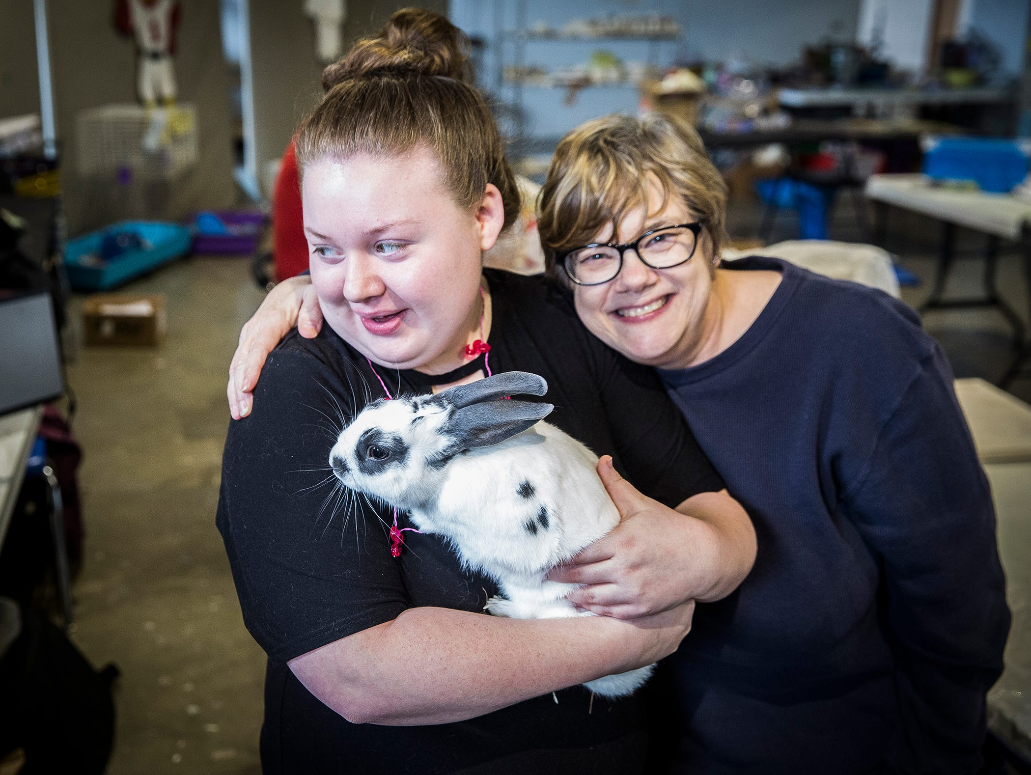 """Beyond I Can workers visit with one of the group's pet rabbits """"Spot"""" at the program's new location in Madjax."""