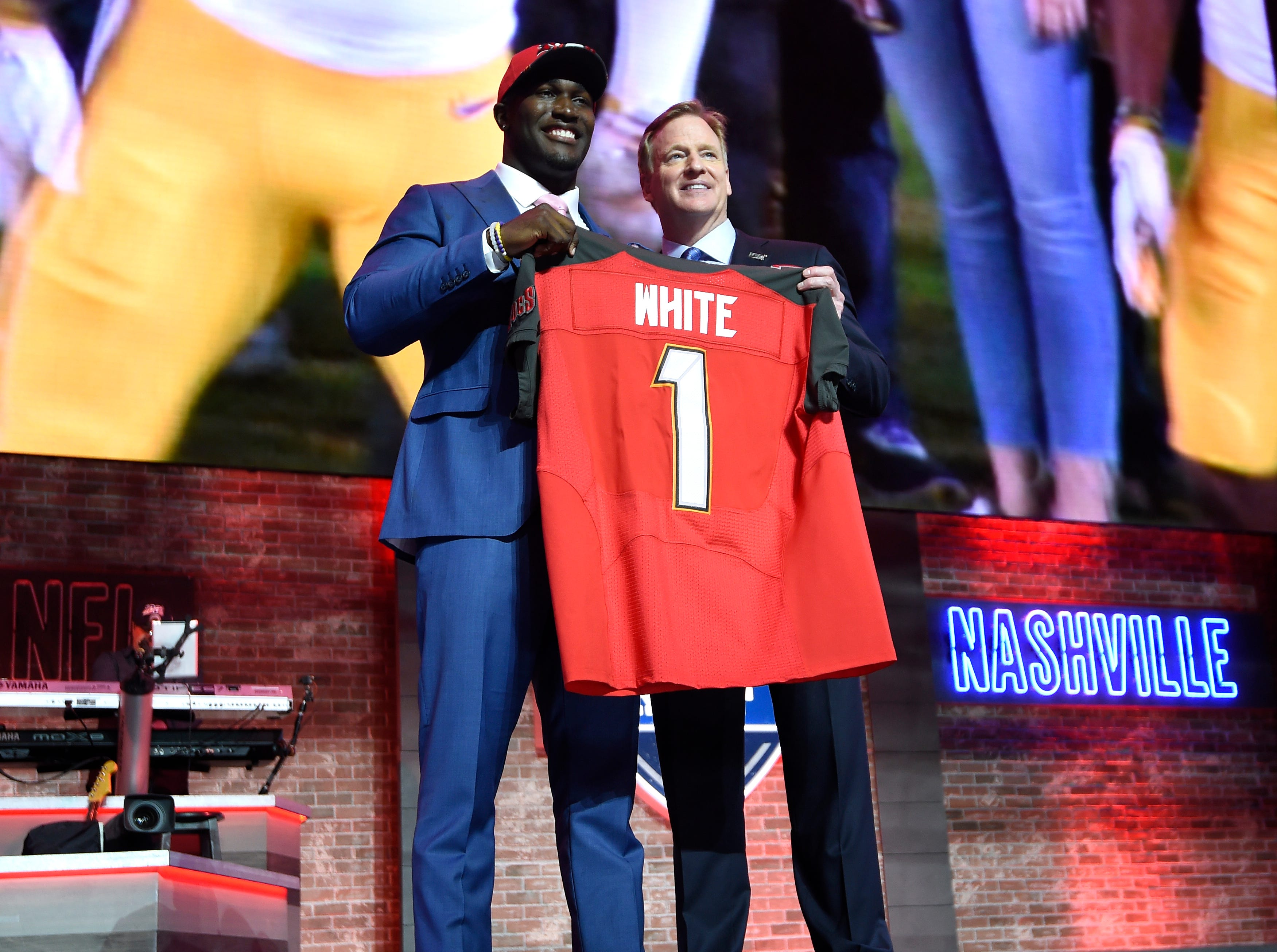 Devin White stands with his new Tampa Bay Buccaneers jersey and NFL Commissioner Roger Goodell during the first round of the NFL Draft Thursday, April 25, 2019, in Nashville, Tenn.
