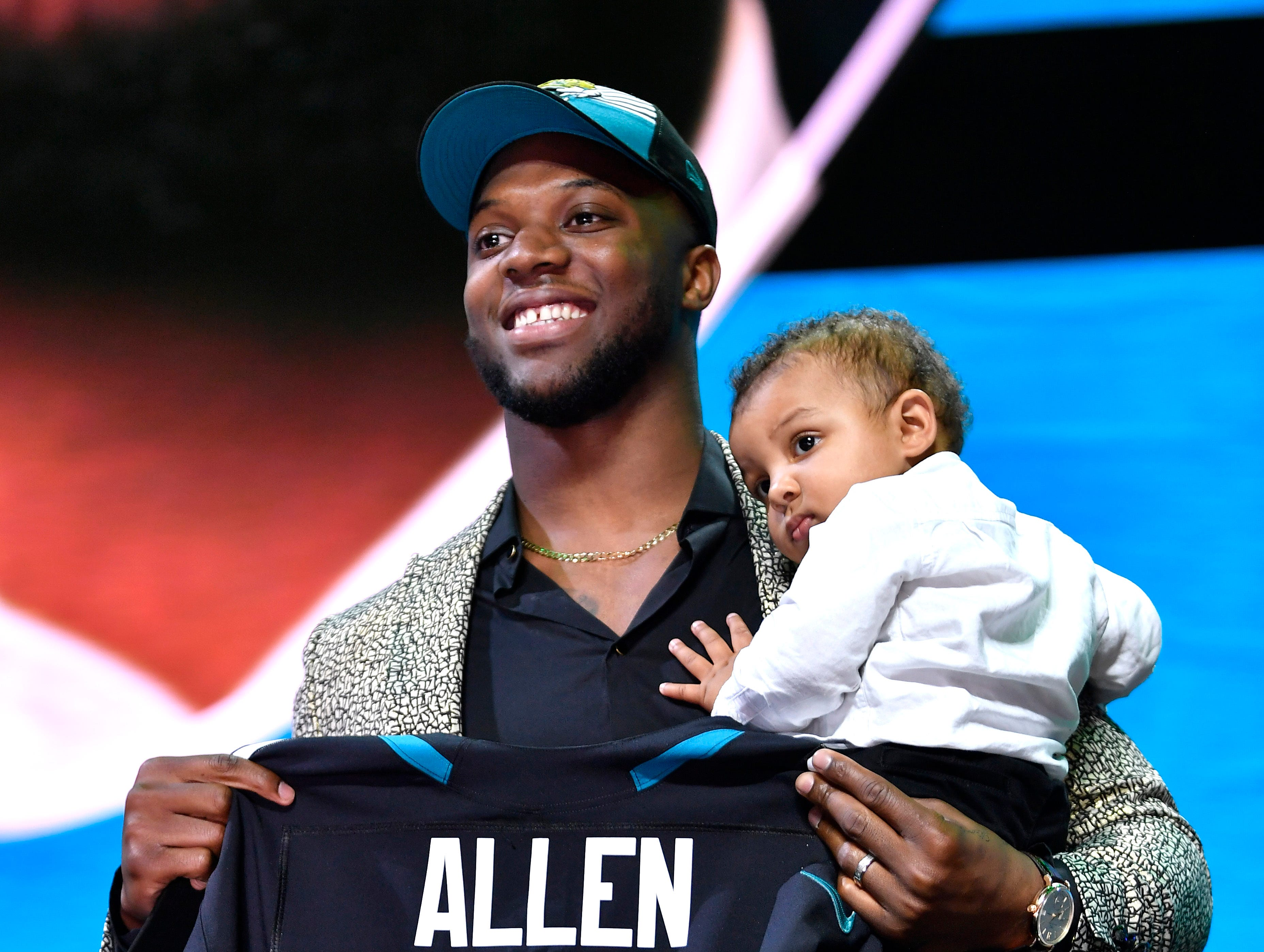 Josh Allen holds his son Wesley and his new Jacksonville Jaguars jersey after being picked during the first round of the NFL Draft Thursday, April 25, 2019, in Nashville, Tenn.