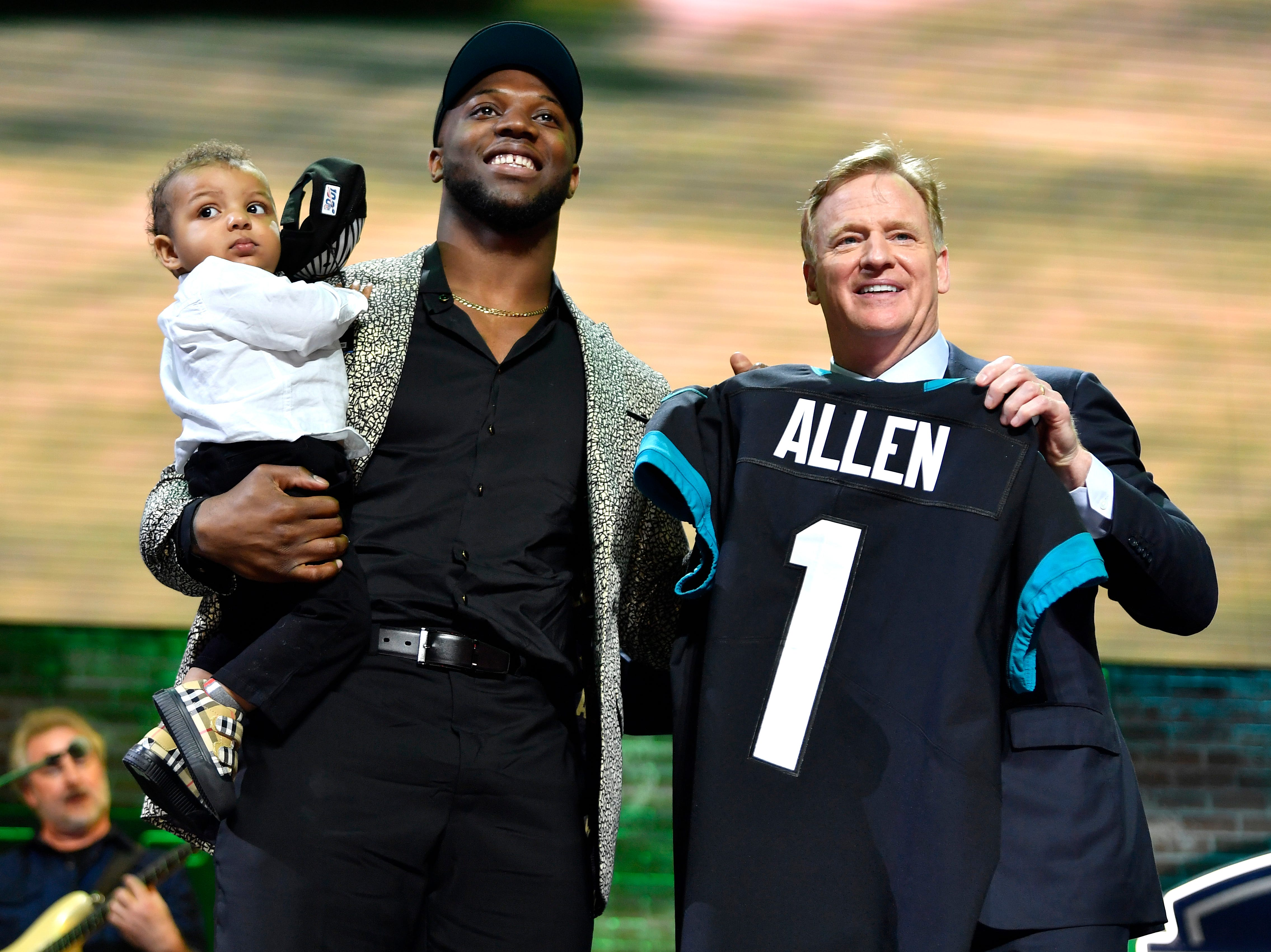 Josh Allen holds his son Wesley after being picked by the Jacksonville Jaguars during the first round of the NFL Draft Thursday, April 25, 2019, in Nashville, Tenn. NFL Commissioner Roger Goodell holds Allen's new jersey