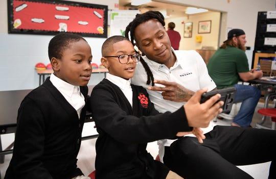Jayden Luke and Jemontez Stewart take a photo with Houston Texans player DeAndre Hopkins at Napier Elementary on Friday.