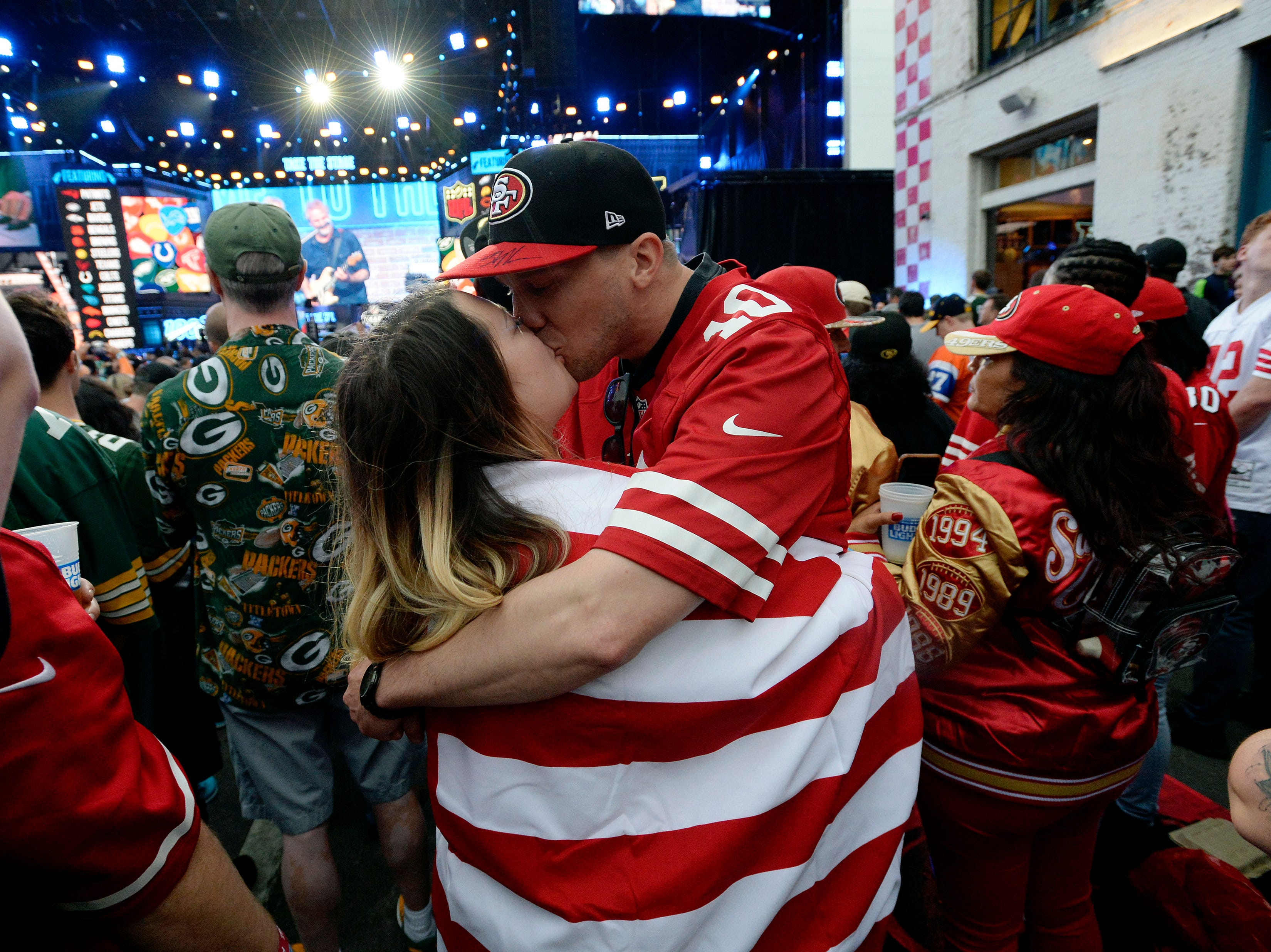 San Francisco fans Stewart Rector kisses Tara Aldrich as they wait for the team to make their draft selection during the NFL Draft on Thursday, April 25, 2019, in Nashville, Tenn.