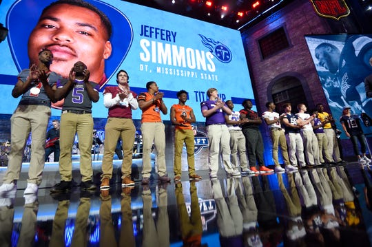 TSSAA athletes applaud the Titans' pick during the first round of the NFL Draft Thursday. Elijah Simmons (sixth from left) caught the attention of the Texans'  J.J. Watt.
