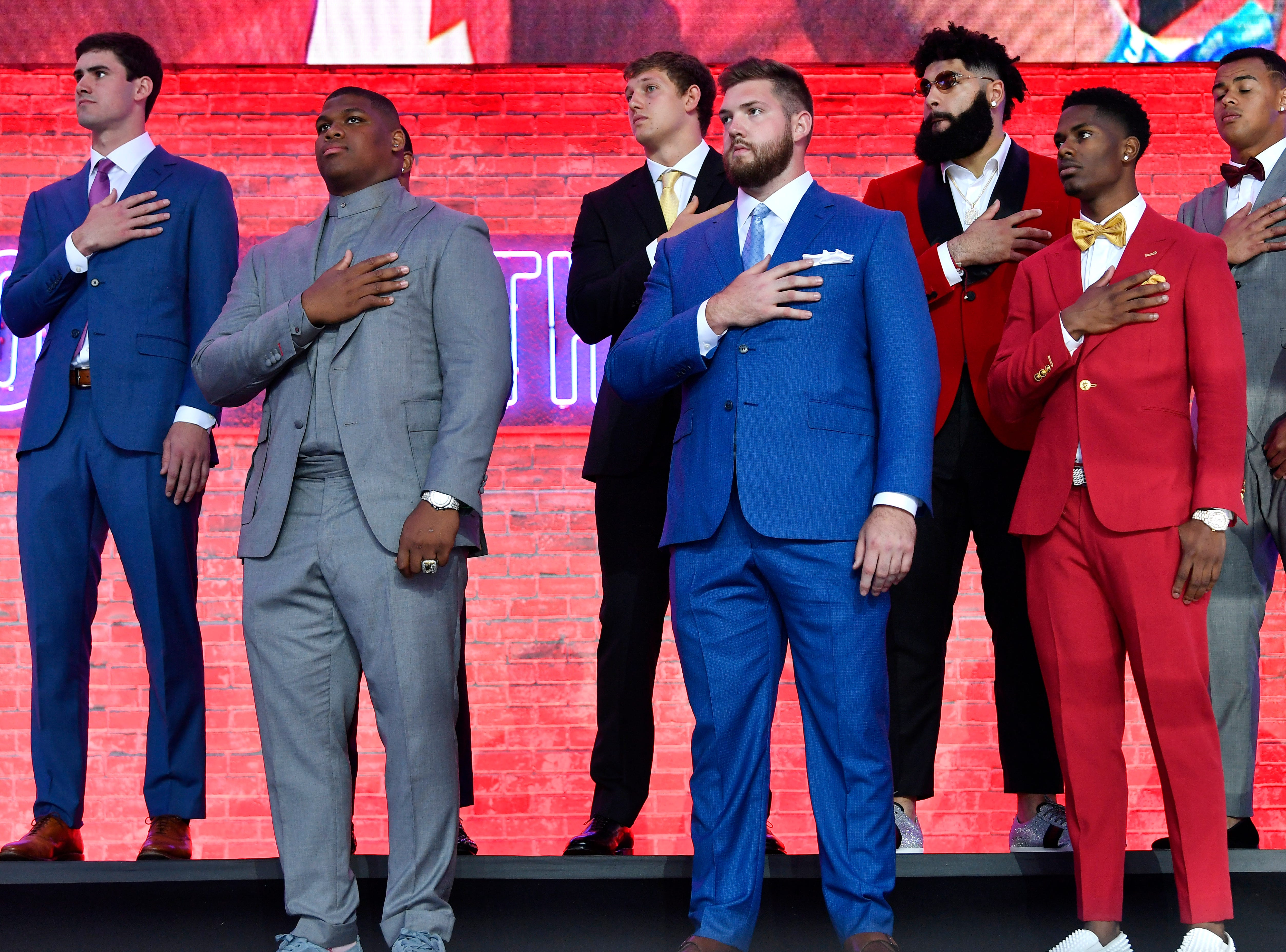 Some of the draft prospects stand for the National Anthem at the start of the first round of the NFL Draft Thursday, April 25, 2019, in Nashville, Tenn.