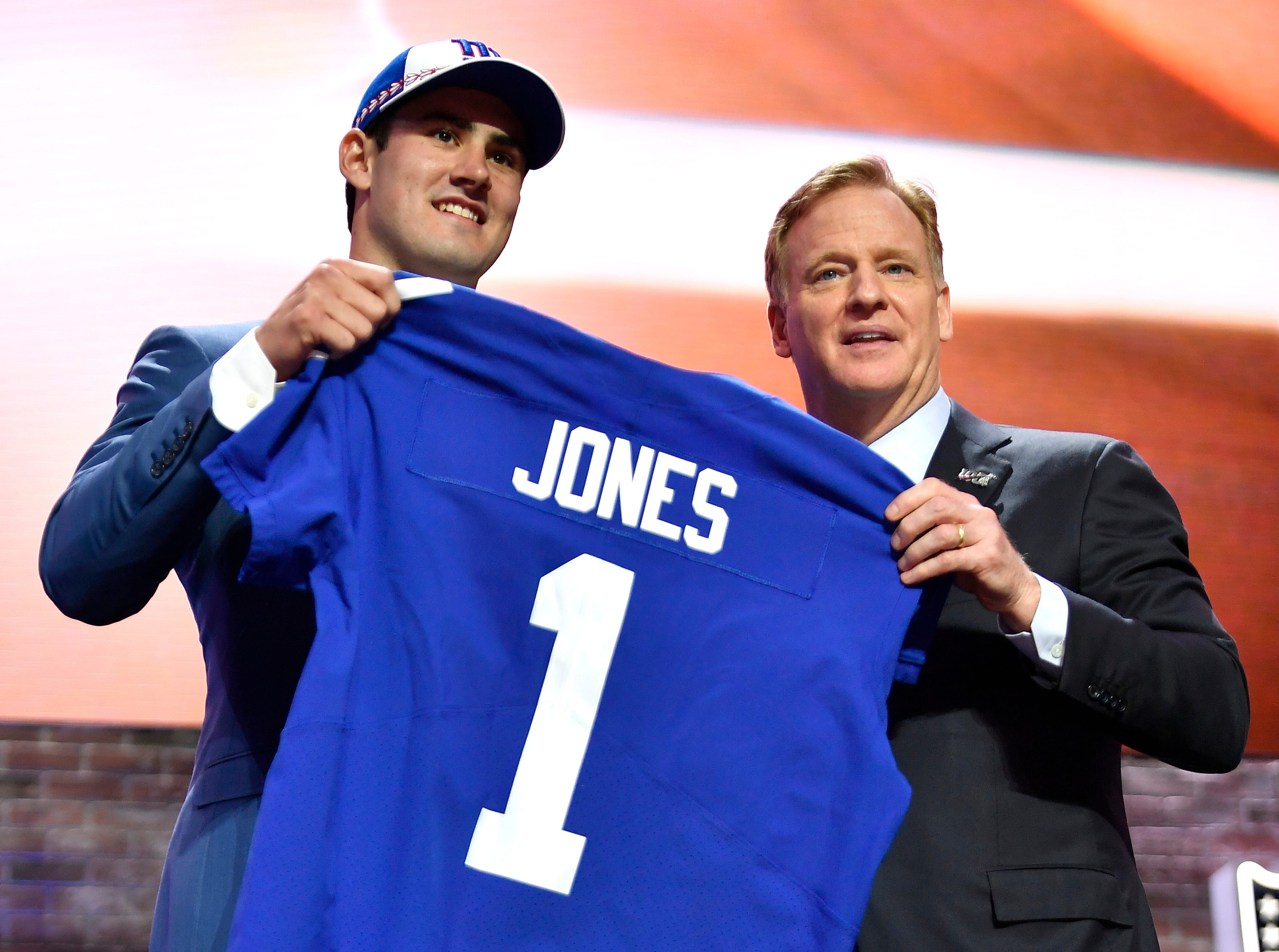 Daniel Jones holds his New York Giants jersey with NFL Commissioner Roger Goodell during the first round of the NFL Draft Thursday, April 25, 2019, in Nashville, Tenn.