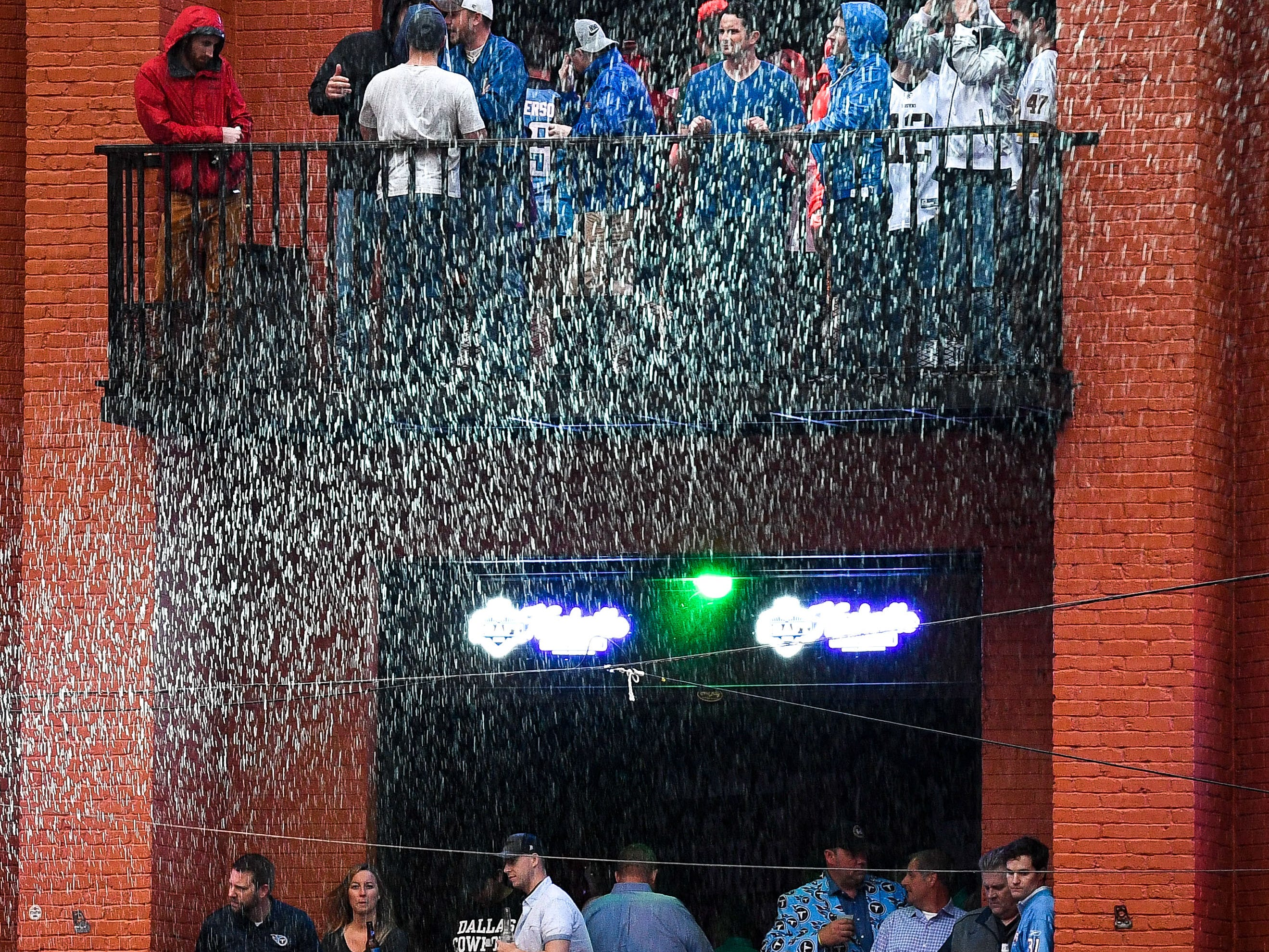 Rain is illuminated by a spotlight outside of Honky Tonk Central during the 2019 NFL Draft on Broadway in Nashville, Tenn., Thursday, April 25, 2019.
