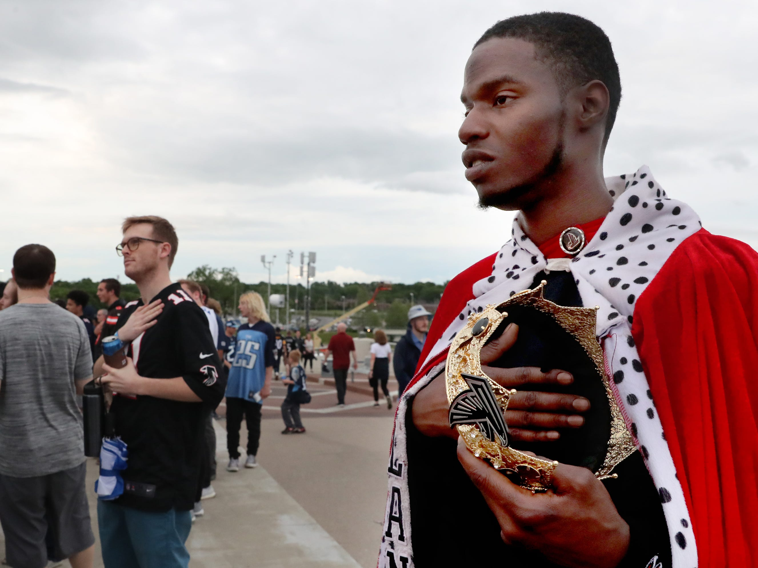 Falcons fan Joseph James, of Atlanta, puts his hand over his heart as the Anthem is performed before the start of the  NFL Draft, while standing on the Seigenthaler Bridge on Thursday, April 25, 2019, in Nashville, Tennessee.