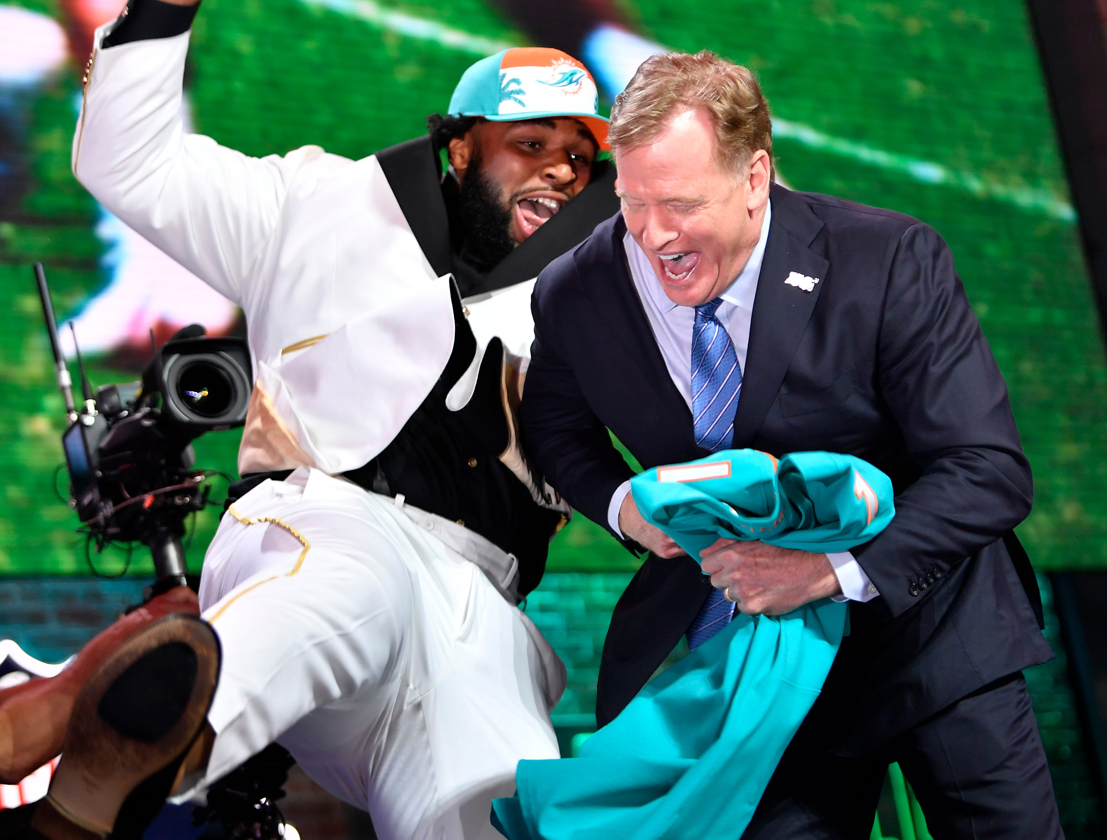 Christian Wilkins celebrates his pick by the Miami Dolphins with NFL Commissioner Roger Goodell during the first round of the NFL Draft Thursday, April 25, 2019, in Nashville, Tenn.