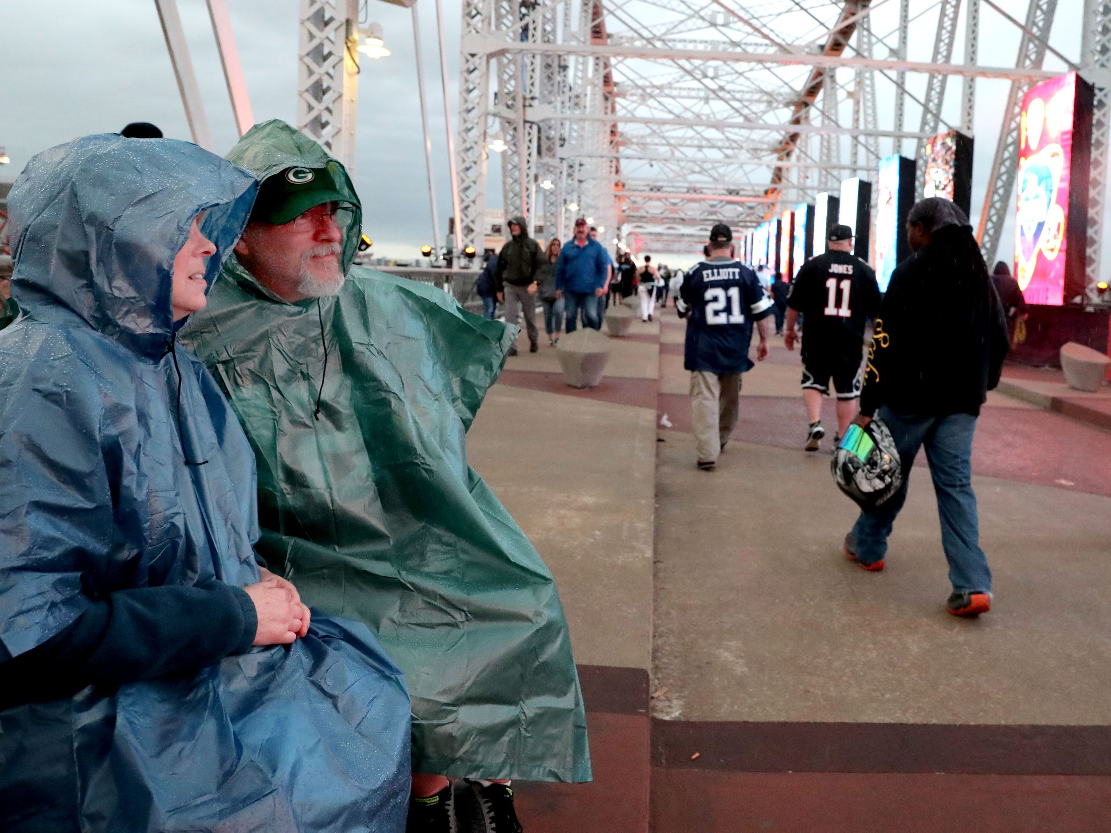 Sherry and Wayne Nisiewicz, both Green Bay fans try to stay dry as they sit on the Seigenthaler Bridge and watch the start of the NFL Draft show as others pass by on Thursday, April 25, 2019, in Nashville, Tennessee.