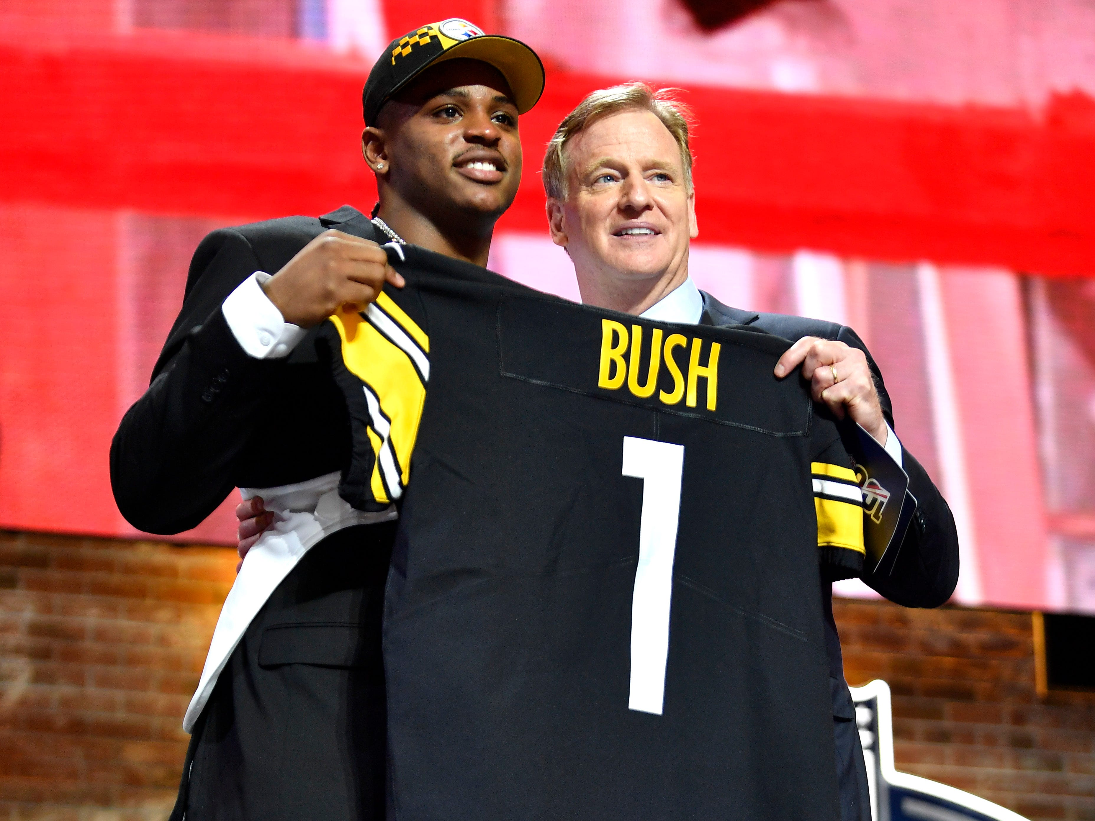 Devin Bush holds his new Steelers jersey with NFL Commissioner Roger Goodell during the first round of the NFL Draft Thursday, April 25, 2019, in Nashville, Tenn.