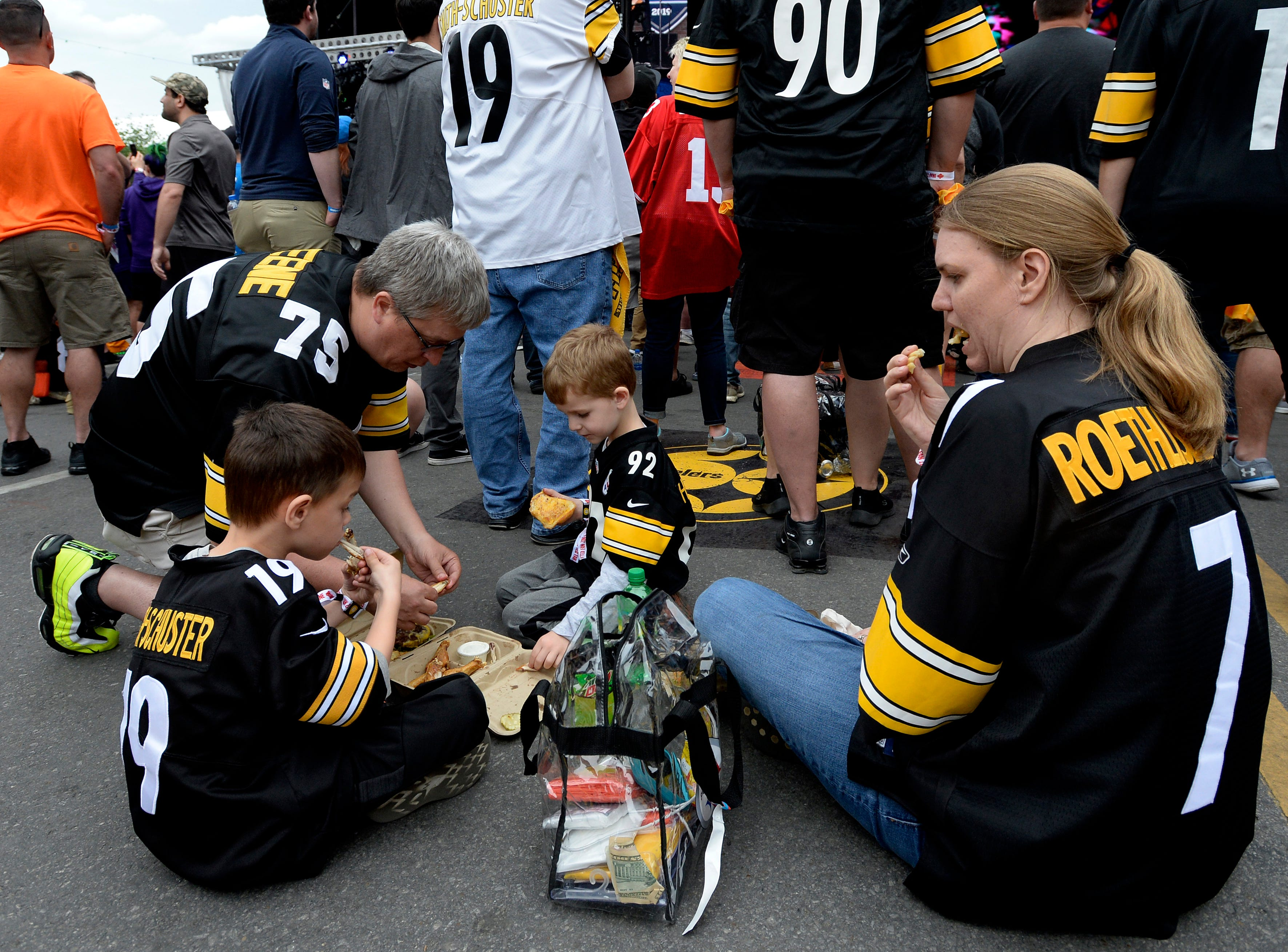 Pittsburgh Steelers fans Declan, 6, Walton, left, his father Dale, Killian, 5, and mother Dana eat on Lower Broadway during the NFL Draft on Thursday, April 25, 2019, in Nashville, Tenn.