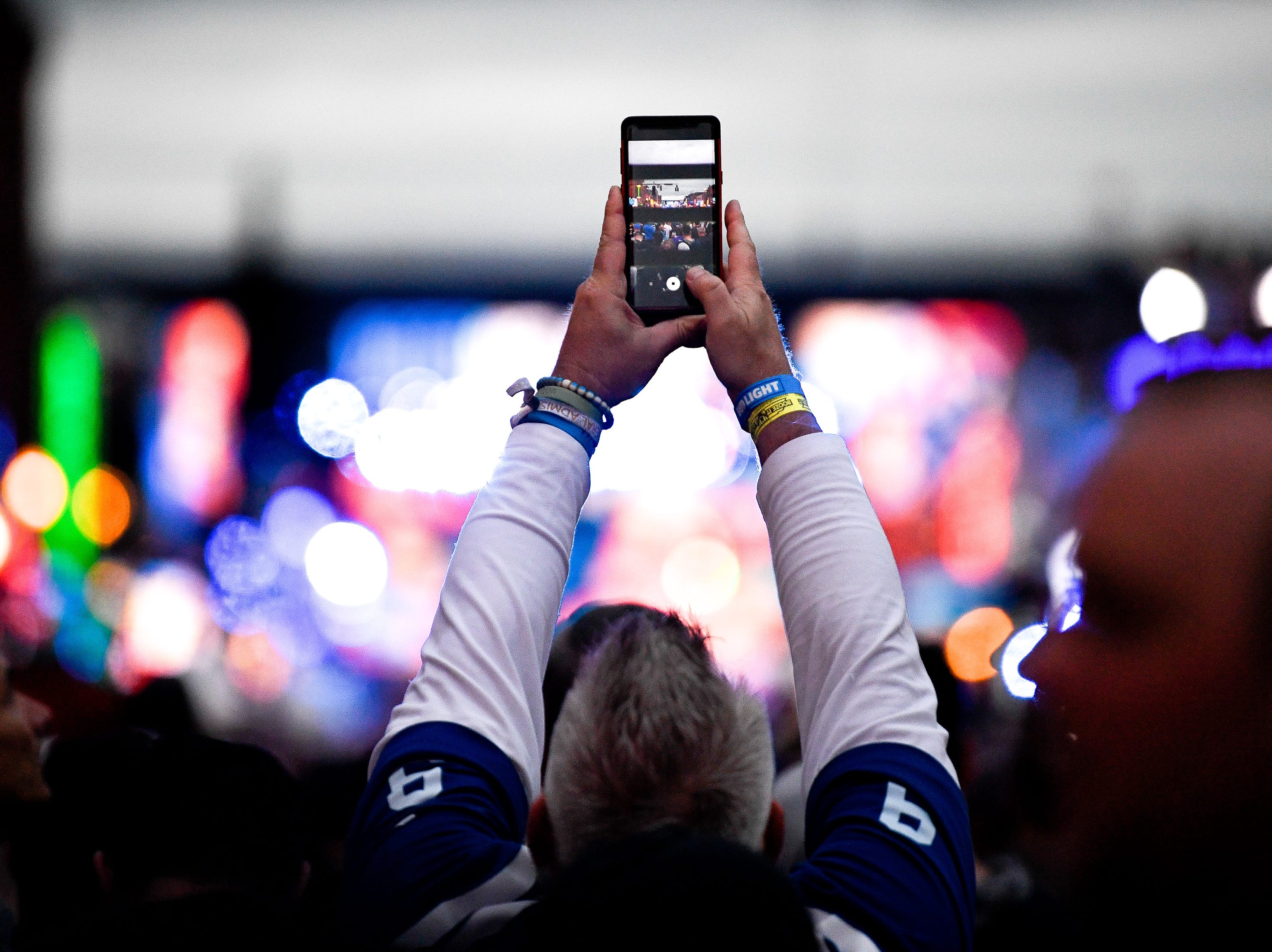 A fan takes a picture with his phone during the 2019 NFL Draft on Broadway in Nashville, Tenn., Thursday, April 25, 2019.
