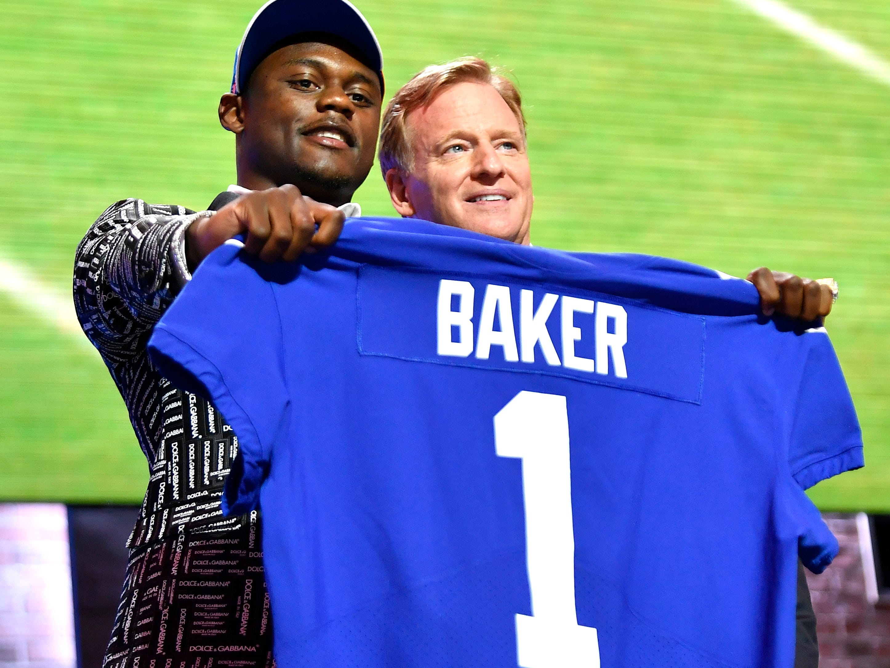 Deandre Baker holds his New York Giants jersey with NFL Commissioner Roger Goodell after being chosen the 30th pick of the first round of the NFL Draft Thursday, April 25, 2019, in Nashville, Tenn.