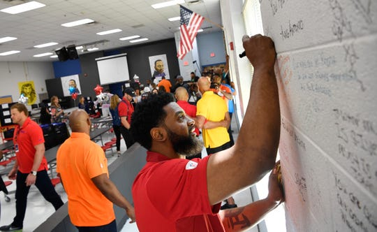 Karlos Dansby writes on the walls of the cafeteria at Napier Elementary on Friday.