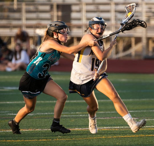 Sophie Sullinger of Naples carries the ball as she battles Rachel Hart of Gulf Coast during the regional quarterfinal game at Naples High on Thursday night.