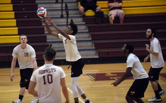 Licking Heights senior Raekwon Rogers sets the ball during a match against Northland on Thursday, April 25, 2019. The Hornets won in three straight sets; 25-16, 26-24, 25-15.