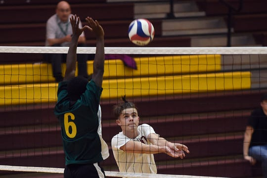 Licking Heights senior Ben Hasson sends the ball past a Northland blocker during a match on Thursday, April 25, 2019. The Hornets won in three straight sets; 25-16, 26-24, 25-15.