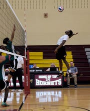Licking Heights senior Daniel Goins spikes the ball at Northland defenders during a match on Thursday, April 25, 2019. The Hornets won in three straight sets; 25-16, 26-24, 25-15.