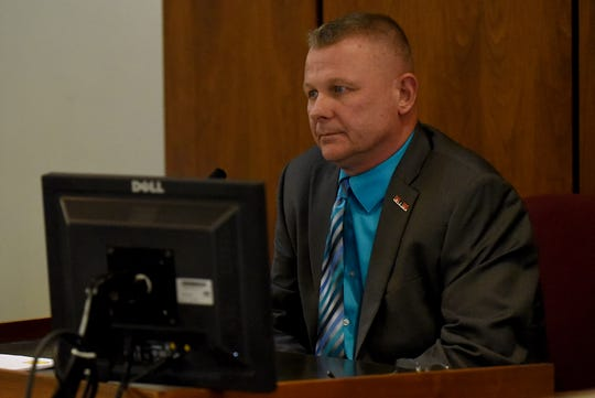 Newark Police Chief Barry Connell reviews stills of video footage from a Newark City Schools' bus while on trial for a traffic citation alleging he passed a stopped school bus in October. Connell was found guilty of passing a stopped school bus and visiting Judge Guy Reece II from Franklin County imposed a $100 fine in court costs.