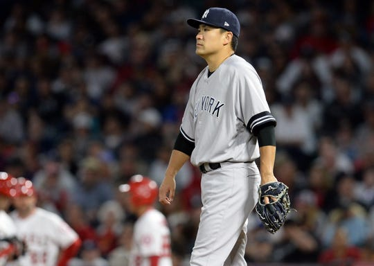April 25, 2019; Anaheim, CA, USA; New York Yankees starting pitcher Masahiro Tanaka (19) reacts before being pulled in the sixth inning against the Los Angeles Angels  at Angel Stadium of Anaheim.