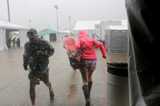 Festival-goers run from the downpour at the WWOZ Jazz tent at the New Orleans Jazz & Heritage Festival New Orleans, Thursday, April 25, 2019. The opening was delayed by heavy rain.