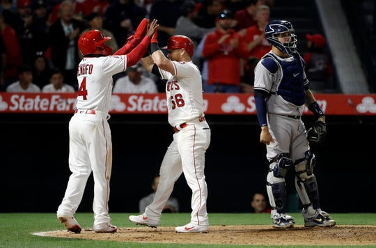 Los Angeles Angels' Kole Calhoun, center, celebrates at home plate with teammate Luis Rengifo, left, after Calhoun's two-run home run during the fifth inning of a baseball game against the New York Yankees Thursday, April 25, 2019, in Anaheim, Calif.