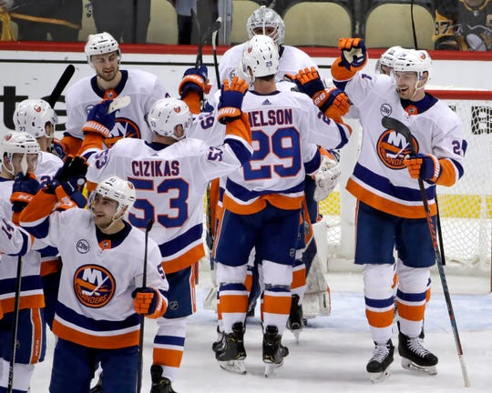 New York Islanders celebrate at the end of Game 4 of an NHL hockey first-round playoff series against the Pittsburgh Penguins in Pittsburgh, Tuesday, April 16, 2019. The Islanders won 3-1, and swept the series. (AP Photo/Gene J. Puskar)