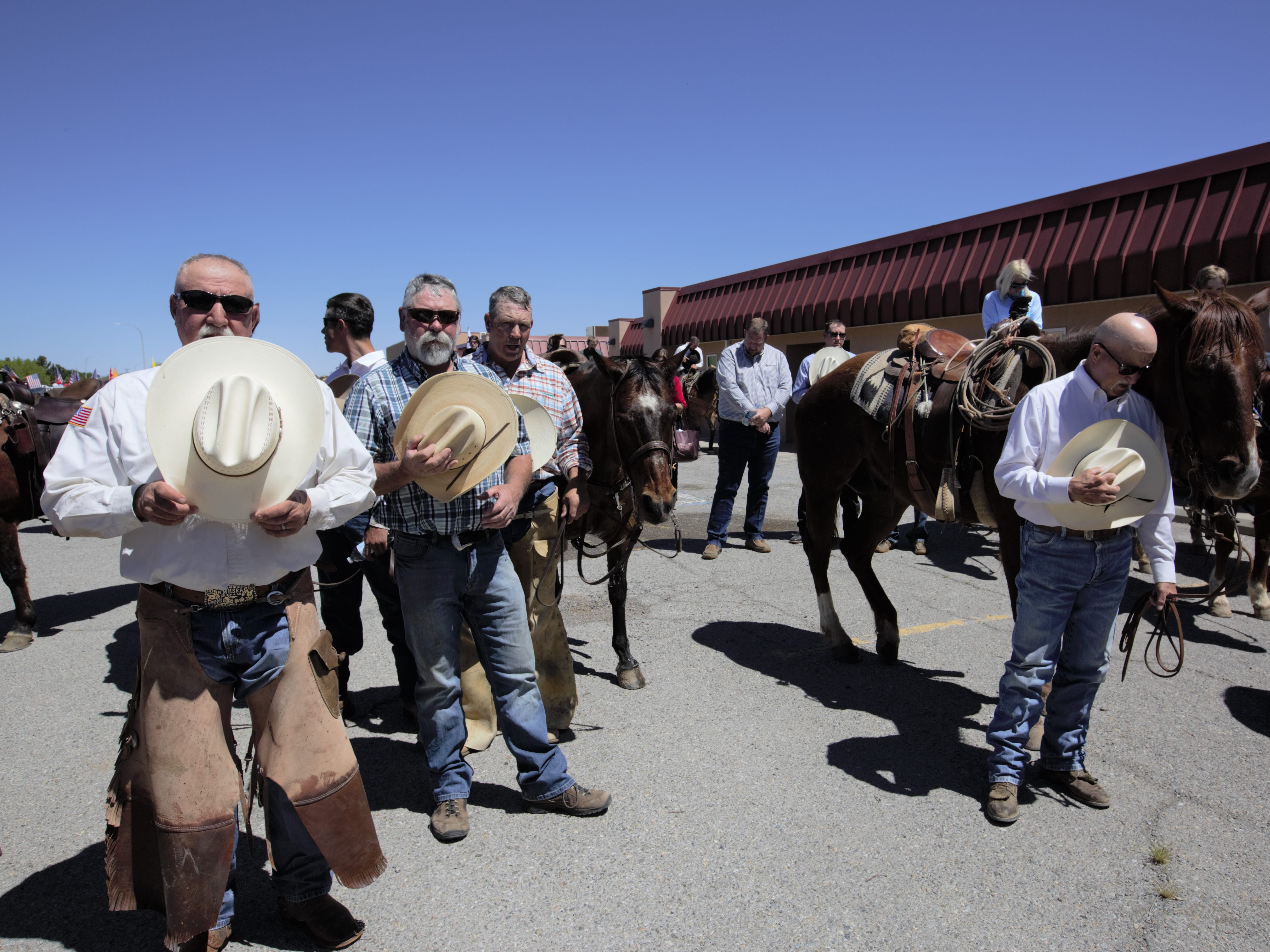 Participants in a Cowboys for Trump event in Las Cruces on Thursday, April 25, 2019 remove their hats for an invocation that launched the rally.