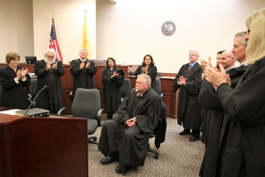 Area District and Magistrate court judges clap for new District Court Judge Curtis Gurley, center, at the end of an investiture ceremony Friday afternoon in Aztec District Court.