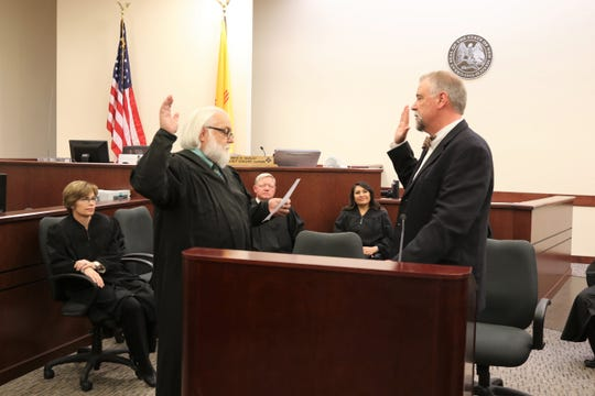 Former District Judge John Dean Jr., left, swears in new District Judge Curtis Gurley during an investiture ceremony Friday afternoon in Aztec District Court as District and Magistrate court judges look on.