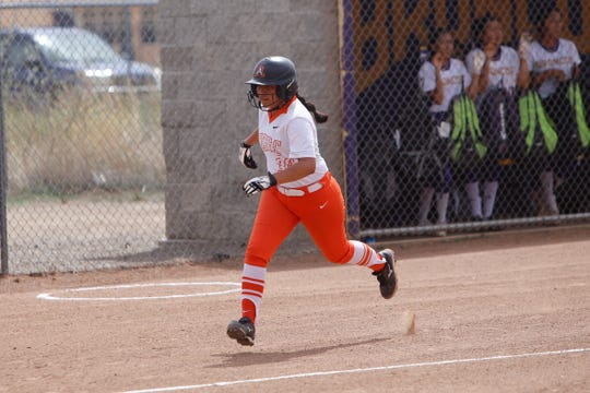 Aztec's April Trujillo darts down the third base line and scores a run against Kirtland Central during Friday's District 1-4A game at KCHS.
