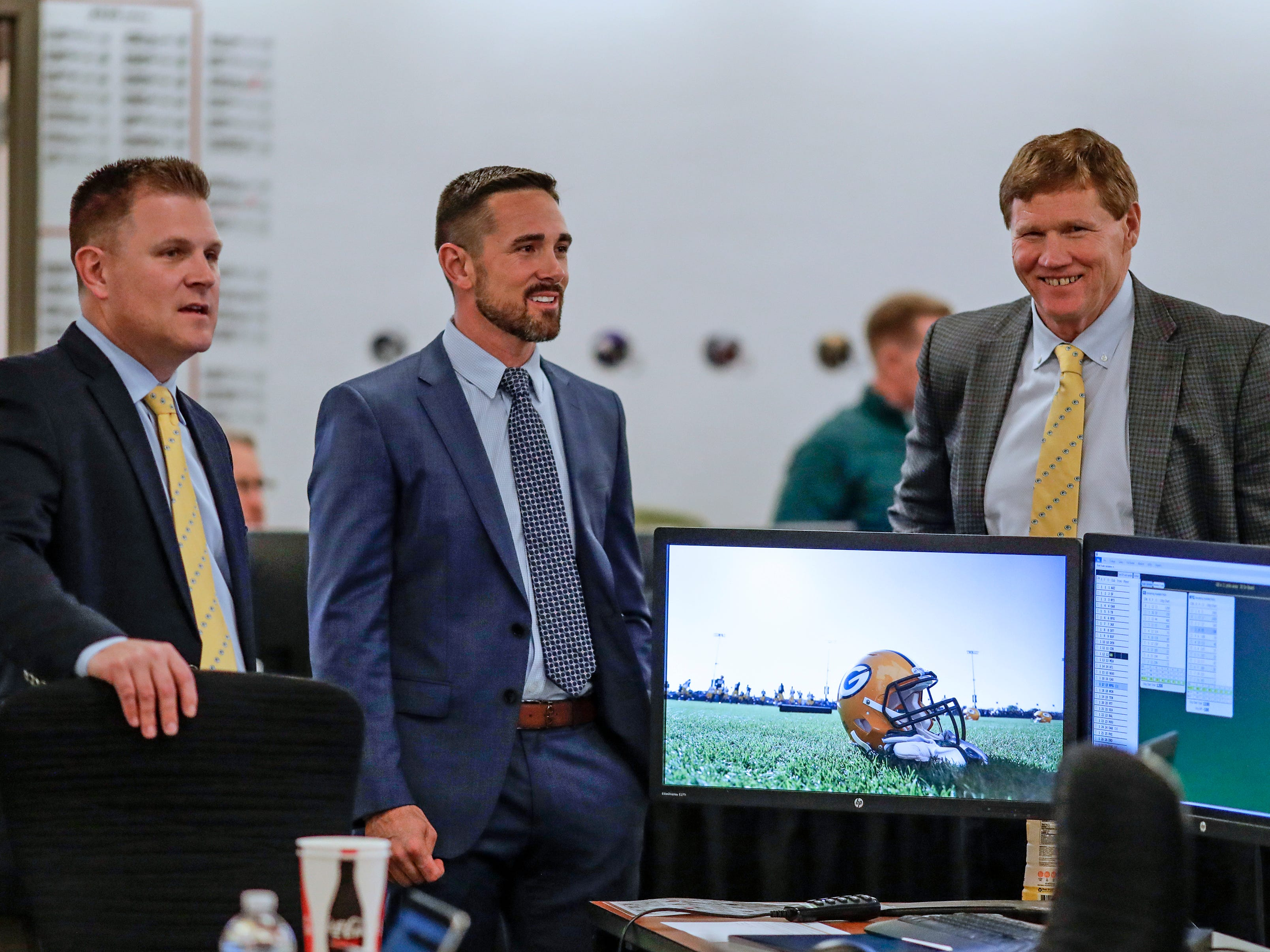 Green Bay Packers general manager Brian Gutekunst, from left, coach Matt LaFleur and president Mark Murphy chat in the team's draft room Thursday night at Lambeau Field in Green Bay.
