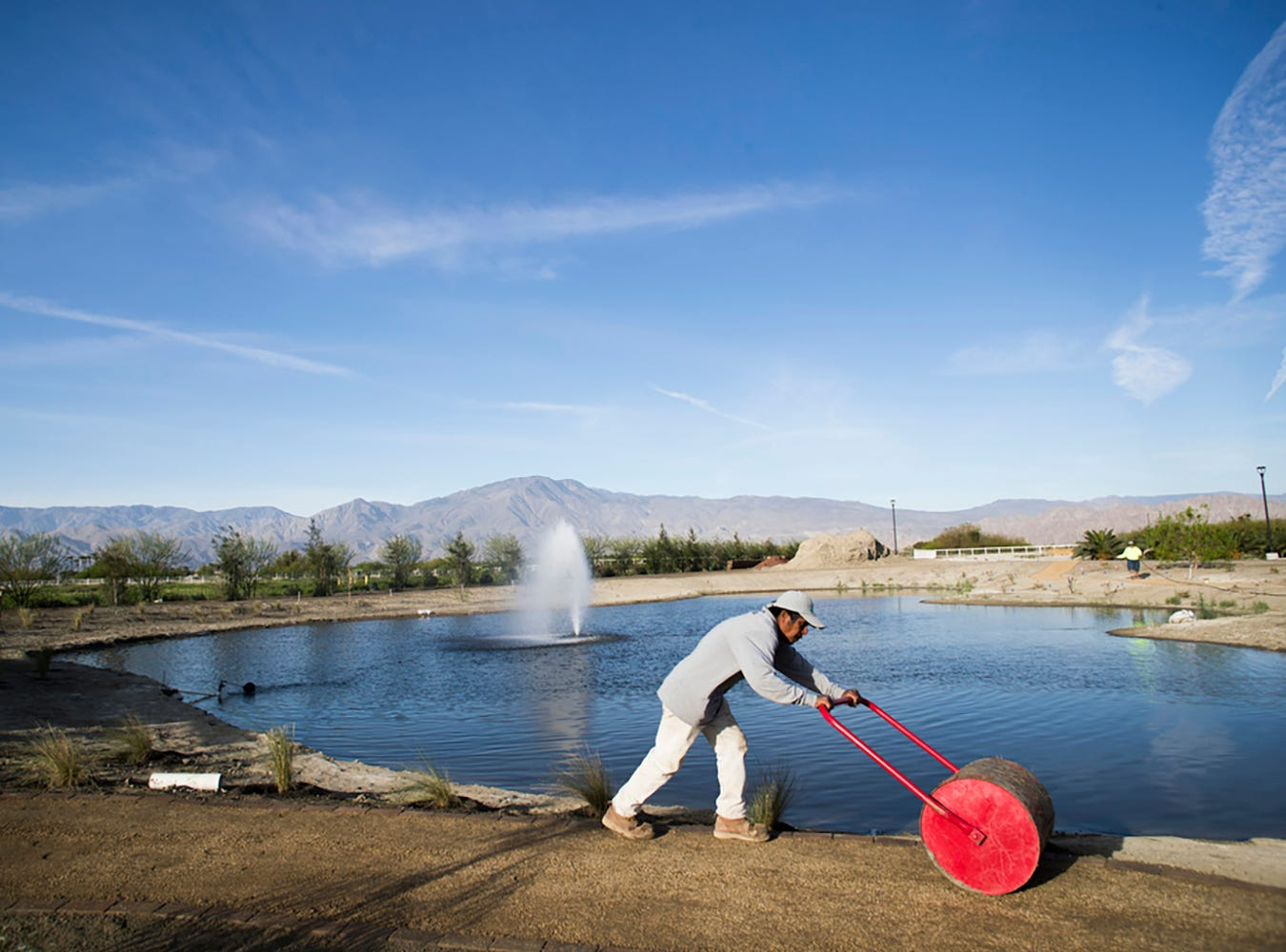 The Augustine tribe is in the final stretch of opening a 33-acre farm on their reservation, featuring a landscaped, exhibition garden. In this photo, a worker flattens out a path near the pond on the organic farm.
