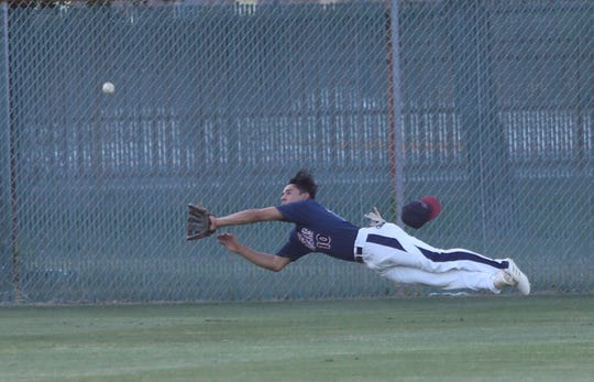 Miles Dille of La Quinta leaps unsuccessfully for a catch during the Desert Empire League baseball championship at La Quinta High School, April 25, 2019.