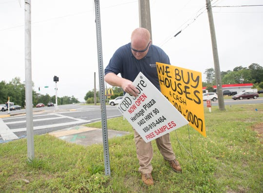 Nathan Bell, a Santa Rosa County code enforcement officer, removes snipe signs from the intersection of U.S. 90 and Woodbine Road on Wednesday.