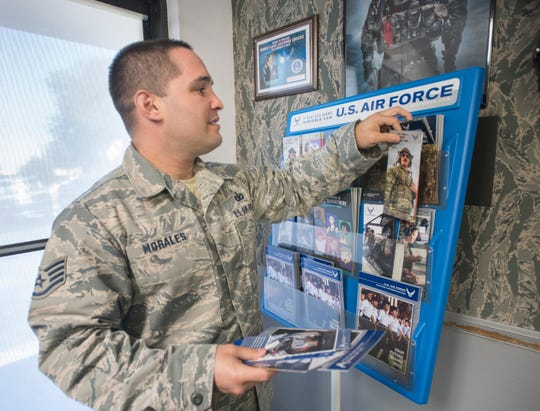 Recruiter Sgt. Carlos Morales pulls brochures at the Air Force recruitment office in Pensacola on Monday, April 22, 2019.