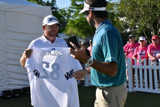 Bubba Watson presents his playing partner J.B. Holmes with a Blue Wahoos jersey prior to beginning their second round of Zurich Classic in New Orleans. It was Holmes' 37th birthday Friday.