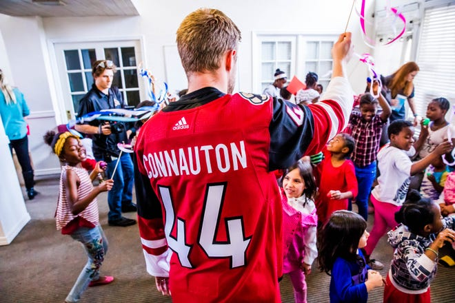 Arizona Coyotes defensemen Kevin Connauton plays with kids at the Phoenician Palms shoe donation.