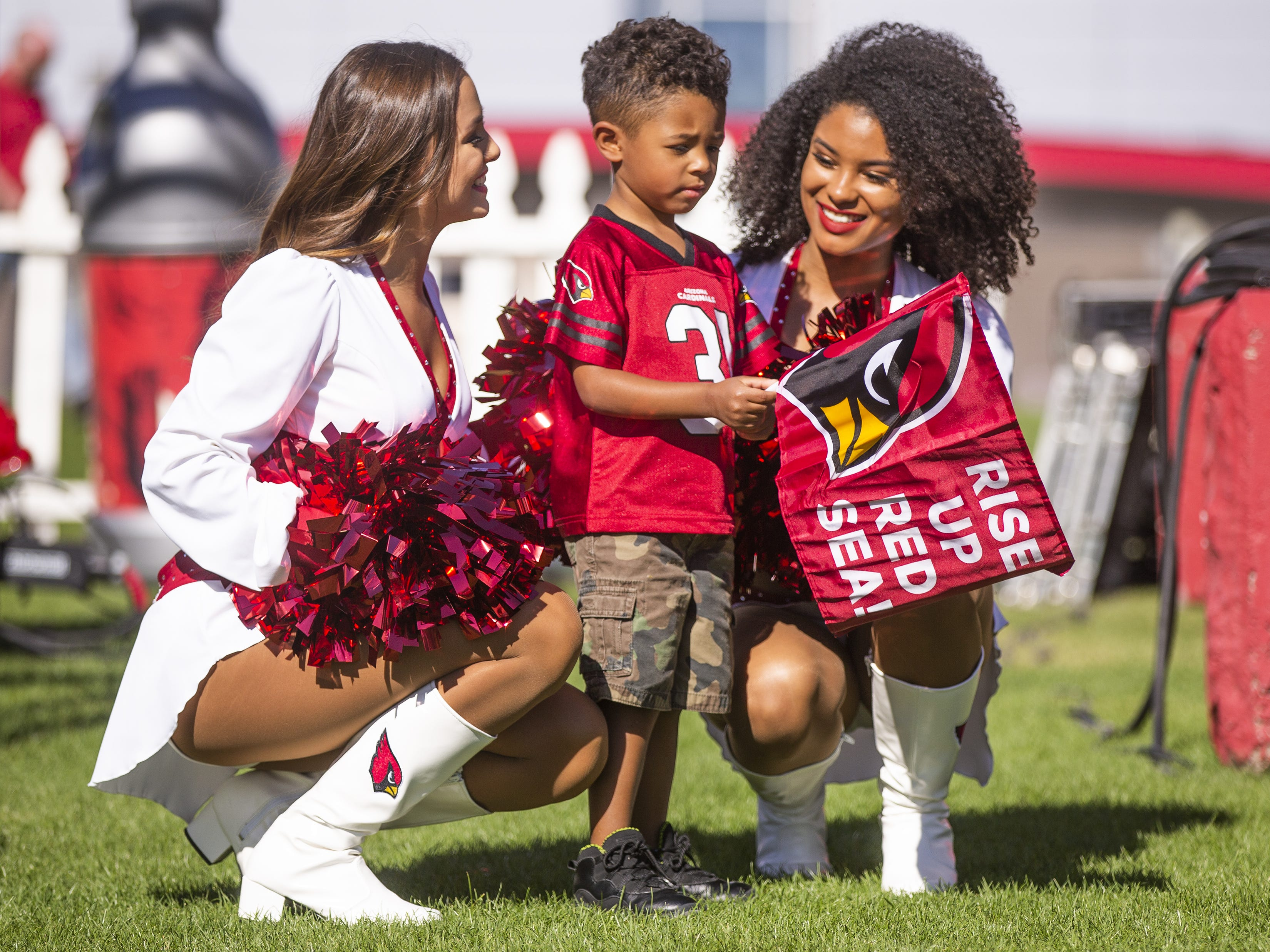 Arizona Cardinals cheerleaders Mandy, left, and Tequasia, right, pose with Isaiah Henry, 3, Peoria, at the NFL Draft party on the Great Lawn outside State Farm Stadium, Thursday, April 25, 2019.