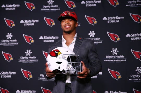 Kyler Murray holds up a Cardinals helmet during an introductory news conference on April 26.