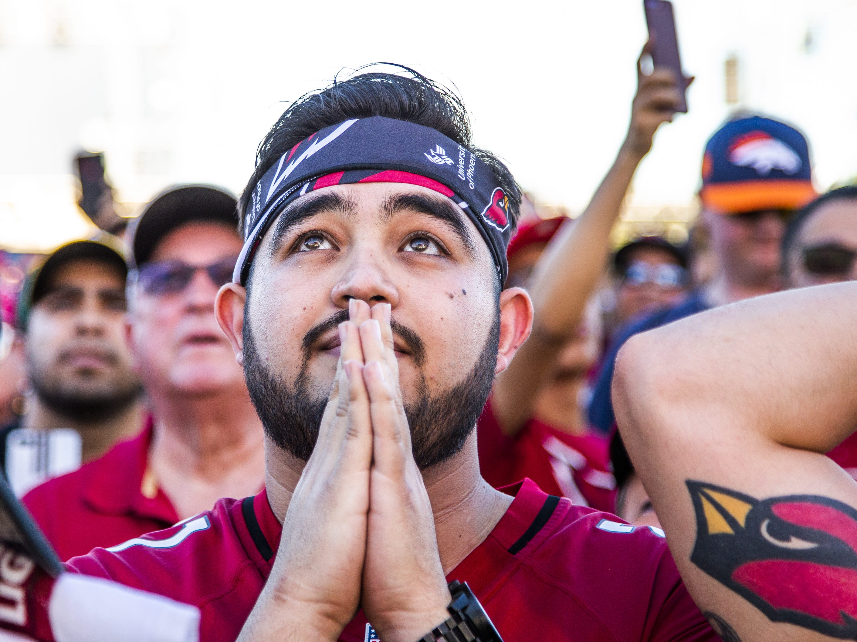 Jesus Cano, 28, Phoenix, waits for the Arizona Cardinals to make their first pick in the NFL Draft during a draft party on the Great Lawn outside State Farm Stadium, Thursday, April 25, 2019.