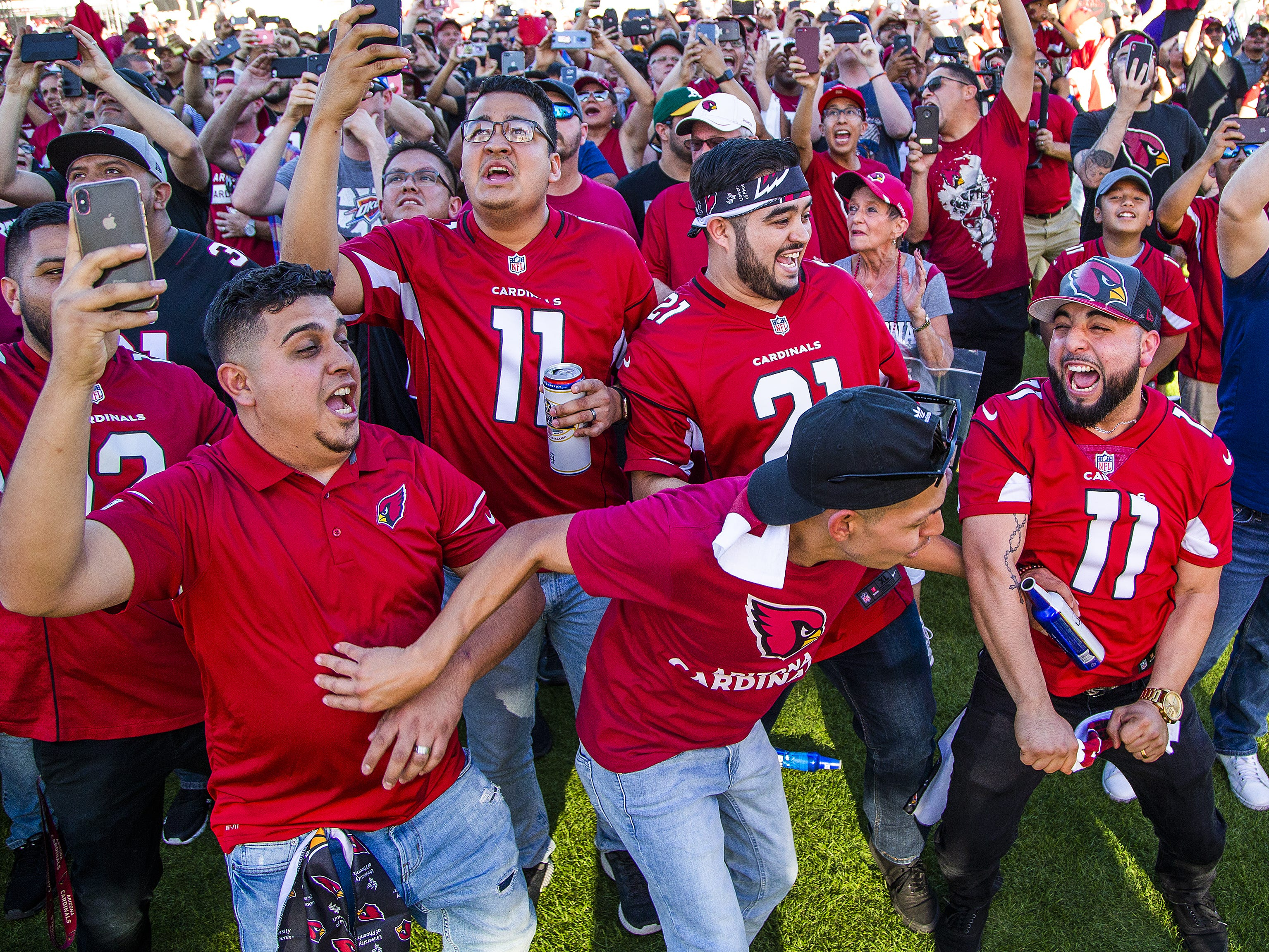 Sergio Rogel, left, Efren Hernandez, Javier Salas, Jesus Cano, and Jesus Quezada, cheer as the Arizona Cardinals make their first pick in the NFL Draft. The fans watched a live feed during a draft party on the Great Lawn outside State Farm Stadium, Thursday, April 25, 2019.